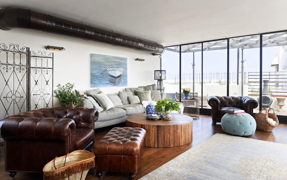 שטיח בגווני אקוורל מתכתב עם הפוף התכלכל והתמונה שמעל הספה. מבט לסלון (צילום: שי אדם)