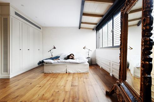 הניקיון היחסי של הפריטים נשבר באמצעות מראה גדולה הנתונה במסגרת עץ מוזהבת עם סלסולים בסגנון עתיק. חדר השינה (צילום: שי אדם)