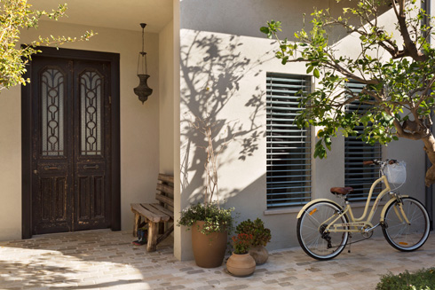 דלת ישנה וספסל במראה משופשף בפתח ביתה של המעצבת קרן גנס (צילום: אסף פינצ'וק)
