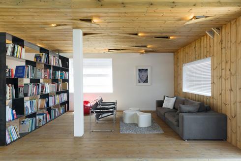 ספריית ברזל חוצצת בין הסלון לשולחן הישיבות. הרהיטים שנבחרו הם קלאסיקות מודרניות (צילום: גדעון לוין)