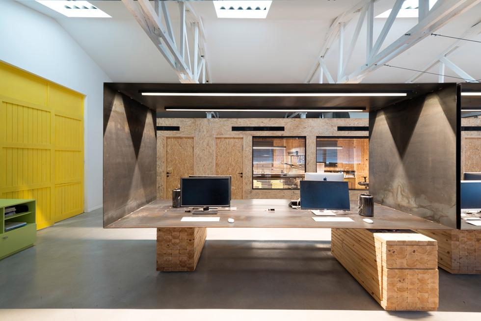 במרכז האולם המלבני של המשרדים תוכננה מסגרת פלדה גדולה ושחורה, שנראית כמרחפת - היא ניצבת על הגבהות עץ ואינה מגיעה לתקרה. כאן נמצאות עמדות העבודה הפתוחות (צילום: גדעון לוין)