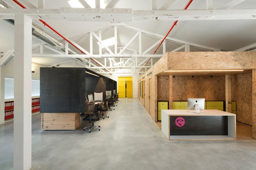 מימין דלפק קבלה ומשרדים שמוקמו בקוביית עץ שעשויה כולה מלוחות OSB. בסוף החלל מובילות דלתות צהובות מקוריות למטבח ולחדר הדפסות (צילום: גדעון לוין)