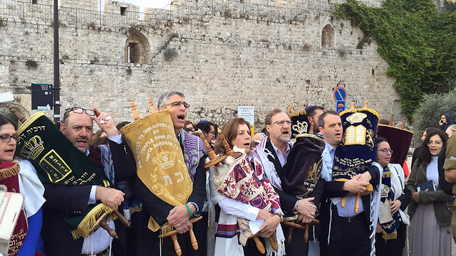 Men and women carry the Torah scrolls