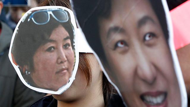 תמונותיהן של הנשיאה פארק ג'ן-הייאה וחברתה הקרובה צ'וי סון-סיל מופיעות בהפגנות המחאה בסיאול (צילום: AP) (צילום: AP)