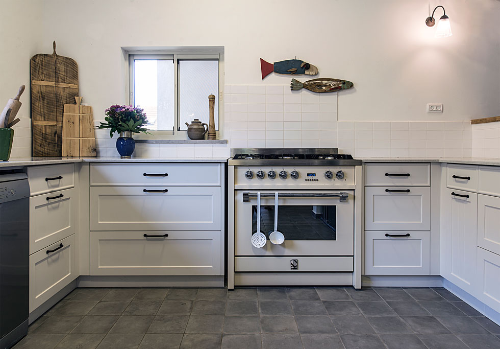 ארונות המטבח תוכננו בסגנון כפרי עם מסגרות וידיות ברזל, ועל הקיר נתלו צמד דגי עץ (צילום: שחר לוי)