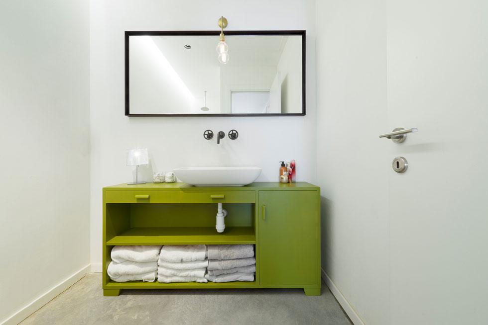 רצפת הבטון המוחלק נמשכת גם בחדר הרחצה. הקירות מטויחים בטיח פגמנטי בלבד, וכארון כיור משמשת שידת וינטג' ירוקה ובוהקת (צילום: גדעון לוין)