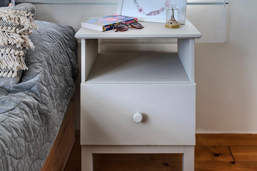 שידת עץ של איקאה נצבעה באפור בהיר והוצבה לצד המיטה (צילום: רותם רוזנאי)