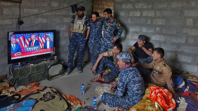 חיילים עיראקים צופים בנאום הניצחון של טראמפ (צילום: AFP)