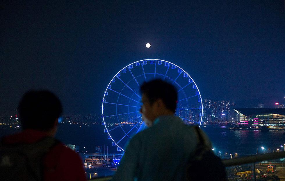 הירח מעל גלגל ענק בהונג קונג (צילום: AFP)