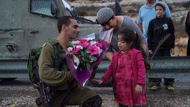 """תהל מגישה פרחים לחיילים שתפסו את המחבלים  (צילום: דובר צה""""ל) (צילום: דובר צה"""