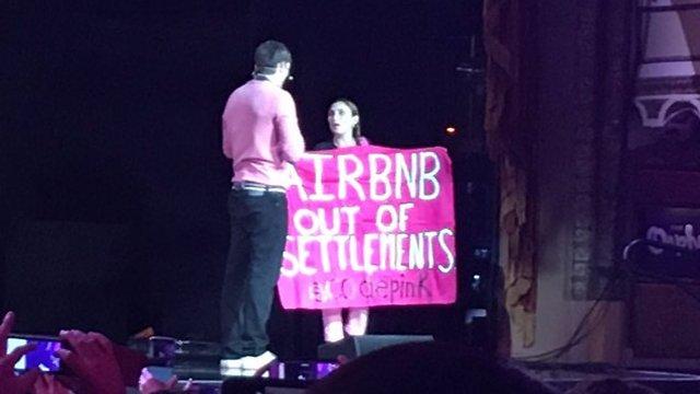 קוצ'ר והמפגינה על הבמה (צילום: מתוך טוויטר) (צילום: מתוך טוויטר)
