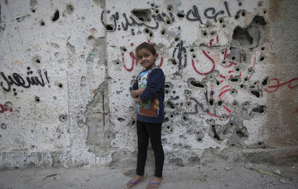 A Palestinian girl poses in front of a wall riddled with bullet marks from the latest Palestinian police offensive in Balata refugee camp (Photo: AP)