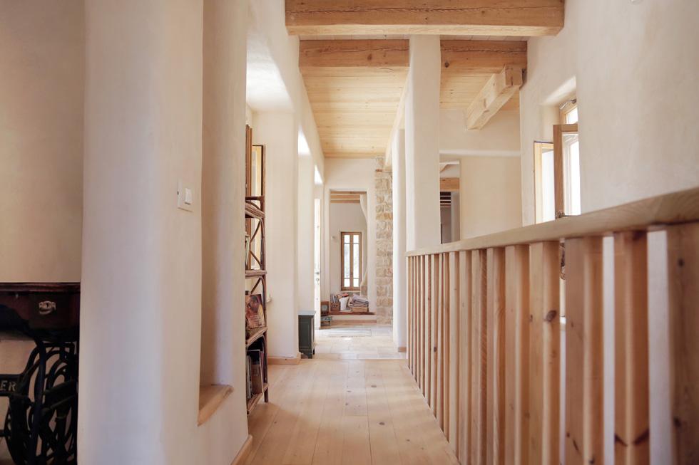 """מבט אל הסלון בקומת הכניסה, שהיא הקומה העליונה של הבית. עובי הקירות החיצוניים הוא יותר מ-50 סנטימטרים, והפנימיים עוביים כ-35 סנטימטרים, מה שמבטיח בידוד טרמי מקסימלי. ''בקיץ'', אומר האדריכל מעוז אלון, """"צונן כאן כמו מרתף של כנסייה'' (צילום: יעלי גבריאלי)"""