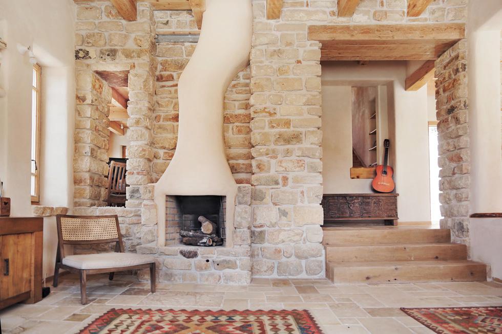 מהאבן המקומית נוסרו גם אריחי הרצפה, והצורה האורגנית של הקמין היא העדפה של בני הזוג (צילום: יעלי גבריאלי)