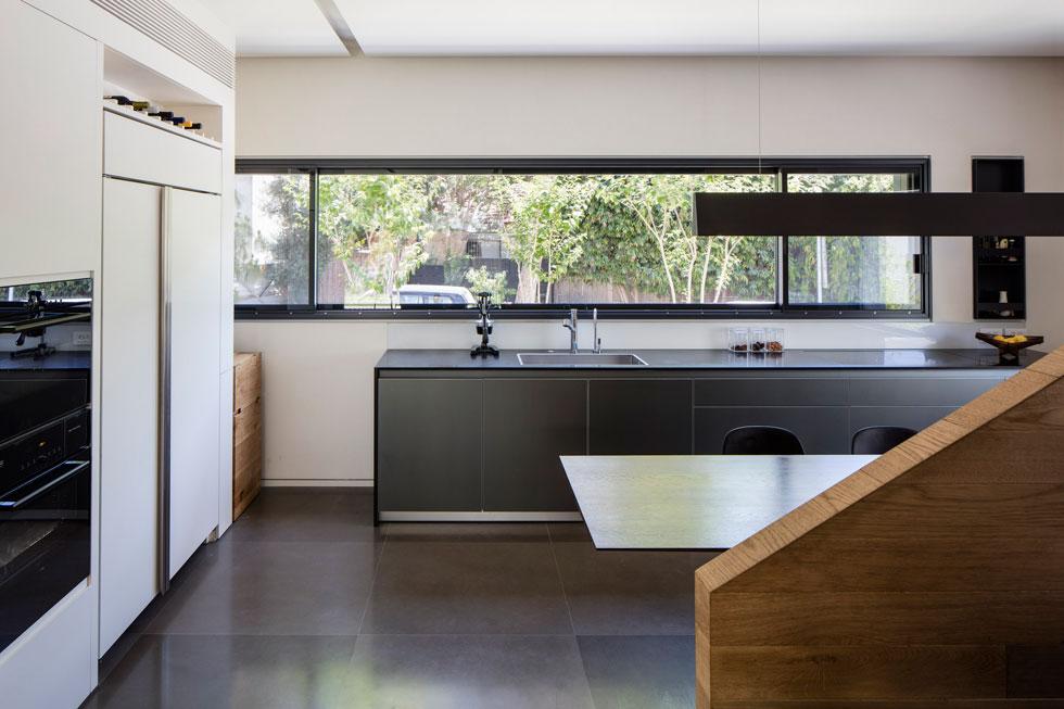 מהצד השני של המדרגות תוכנן המטבח, עם משטח עבודה כהה מתחת לחלון הסרט, וארונות בהירים שעוטפים את המזווה ואת שירותי האורחים (צילום: עמית גירון)