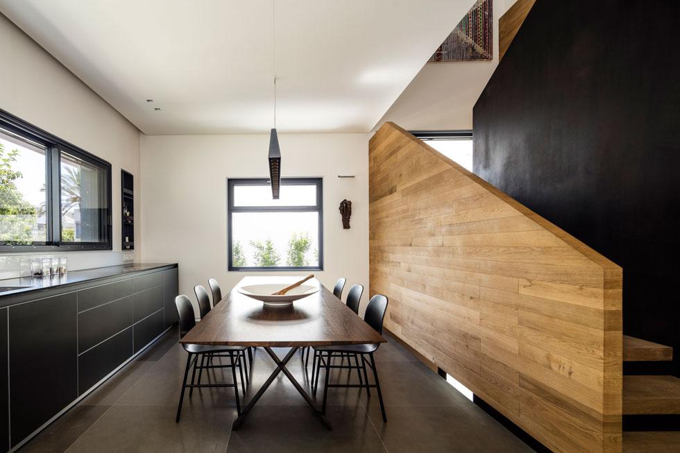 במרכז המטבח שולחן אוכל גדול דיו לאירוח, ומעליו מנורת Tagliata של האדריכל השווייצרי פיטר צומטור. על הקיר בפינה נתלה פסל של יעקב דורצ'ין (צילום: עמית גירון)