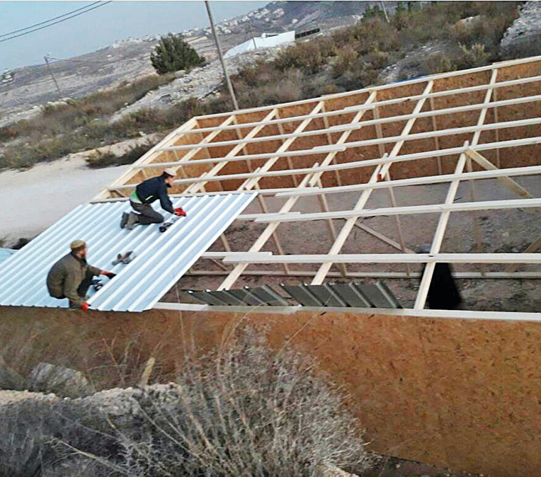 Volunteers building temporary structures in Amona