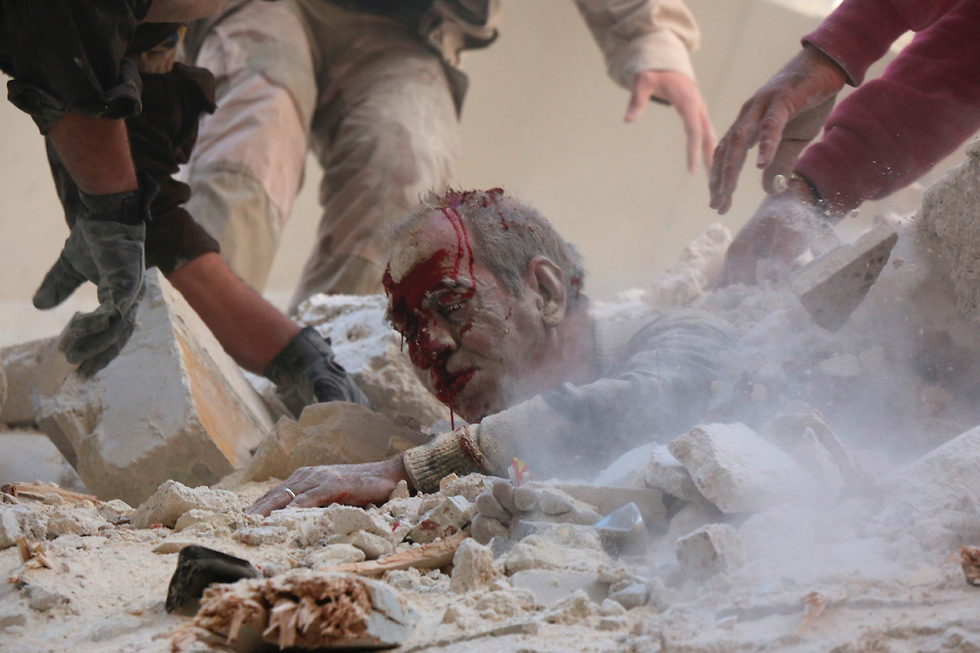 A wounded man being pulled out of the wreckage after bombardments in Aleppo (Photo: AFP)