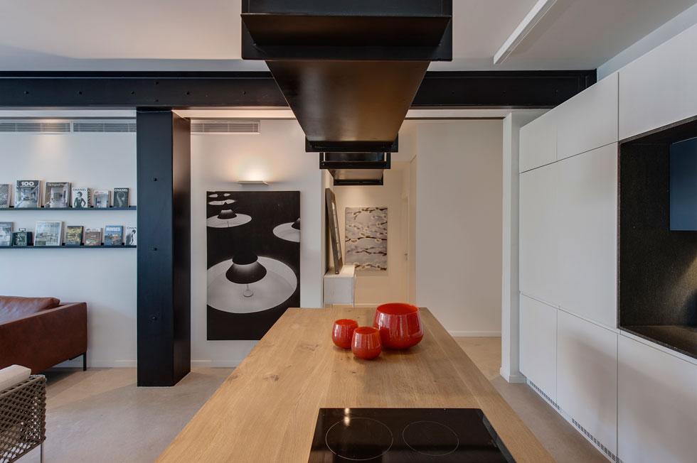 המעבר לחלק הפרטי של הדירה נמצא מצדה השני של המבואה. בגלל מרכזיותו עוצב המטבח כקוביית ארונות לבנה, כשכל מכשירי החשמל חבויים (צילום: עודד סמדר)