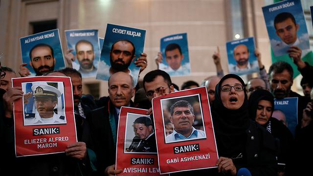 מפגינים מחוץ לבית המשפט עם תמונות הנתבעים וההרוגים (צילום: AP) (צילום: AP)