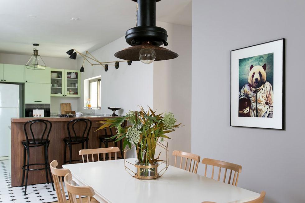 הסלון, פינת האוכל והמטבח מוקמו לאורך קיר מרכזי, שבו שני פתחים המובילים אל החלק הפרטי של הדירה (צילום: שירן כרמל)
