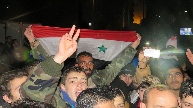Syrian flag waved in Aleppo after the city is captured from the rebels (Photo: AFP)