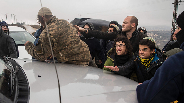 רכבו של גלנט מוקף בצעירים, הבוקר בעמונה (צילום: AFP) (צילום: AFP)