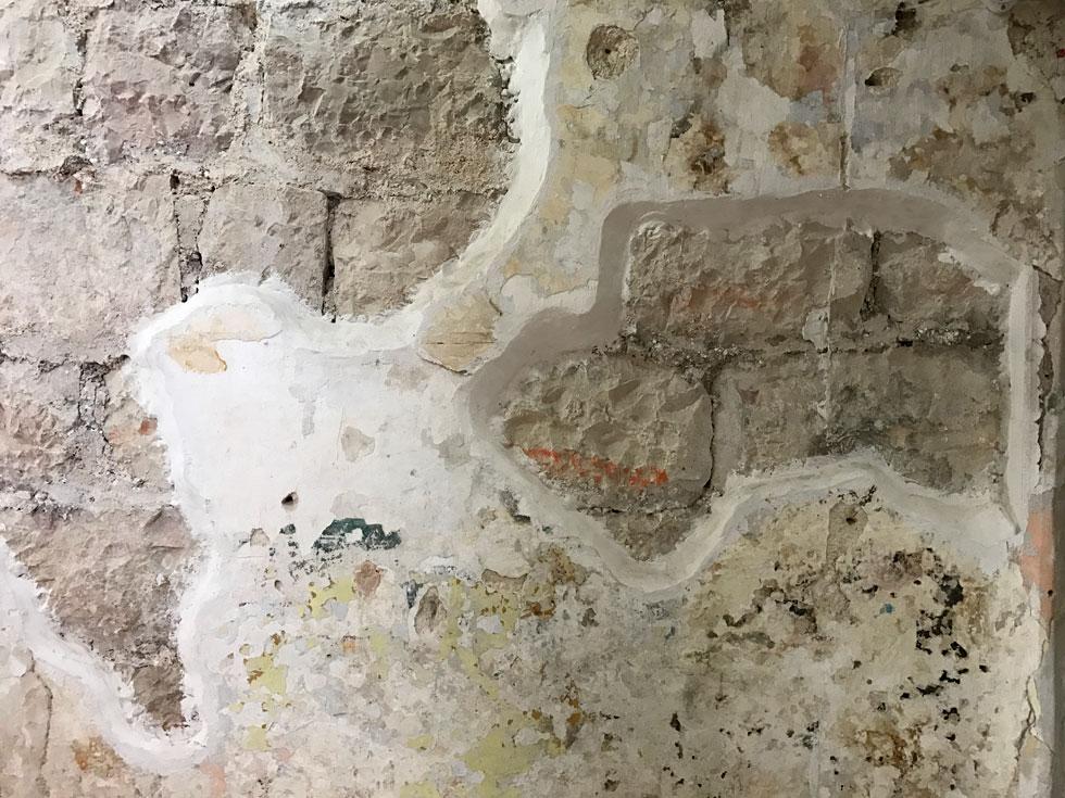 הבניין מיועד לשימור מקיף. עד שזה יקרה, קירות האבן שהטיח נשר מהם עברו שימור זמני כדי לאפשר לדיירים את השימוש במבנה (צילום: הילה שמר)