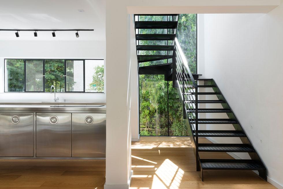 גרם מדרגות קל מפלדה, עם מדרכי פח-מרוג תעשייתי, ממוסגר בחלון הגדול שמאחוריו (צילום: גדעון לוין)