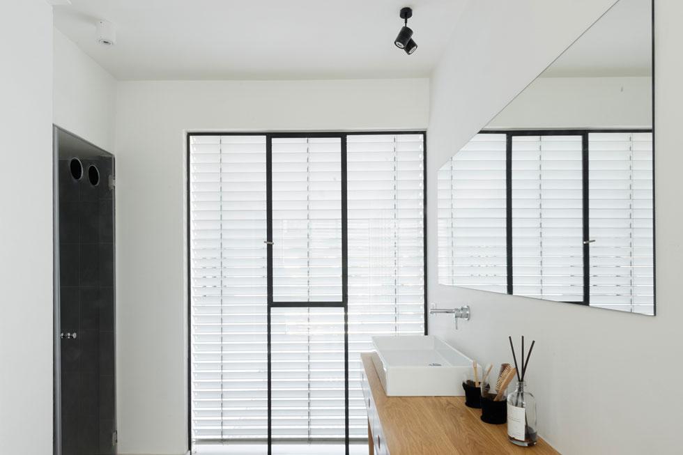 חדר הרחצה של ההורים. מול הכיור, בשני תאים עם דלתות זכוכית, נחבאים השירותים והמקלחת המרווחת (צילום: גדעון לוין)
