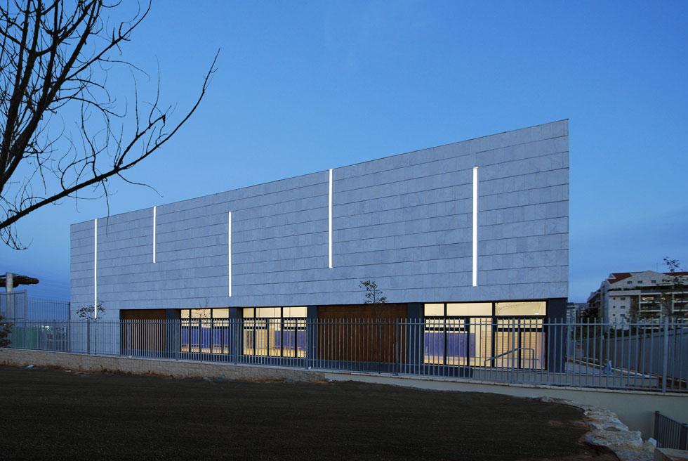 פסי התאורה בחזית אולם הספורט שוברים בשעות היום את החיפוי האופקי ובשעות הלילה מאירים את בית הספר למרחקים (צילום: יואב פלד)