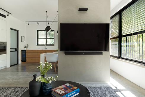קיר חופשי מסתיר עמוד תומך ומשמש גב למסך (צילום: גדעון לוין)