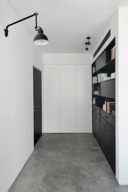 מבואה באפור (רצפת בטון), לבן (קירות וארון מעילים) ושחור (הדלת והספרייה) (צילום: גדעון לוין)