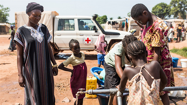 פליטים ממלאים מים בג'ריקנים במחנה מפוקו. אלפי בני אדם נאלצו לברוח מעיר הבירה בנגי ולעזוב את בתיהם בעקבות האלימות שהתפרצה במדינה מאז דצמבר 2012 (Virginie Nguyen Hoang / ICRC) (צילום: הוועד הבינלאומי של הצלב האדום)