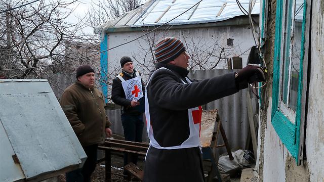 עובד בחטיבת המים ותנאי המחיה של הוועד הבינלאומי של הצלב האדום בשיתוף הצלב האדום האוקראיני מודדים בית שנפגע במחוז דונייצק כדי להתאימו מחדש למגורים. יותר מ-9,000 בני אדם נהרגו בלחימה שפרצה במזרח אוקראינה באפריל 2014 בעקבות המהפכה שבה הודח הנשיא הפרו-רוסי ויקטור ינוקוביץ' ובמקומו עלה בקייב שלטון פרו-מערבי (Orlov/ICRC Yurii) (צילום: הוועד הבינלאומי של הצלב האדום)
