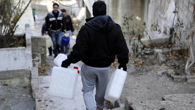 A Syrian man takes Jerrycans to be filled with water (Photo: EPA)
