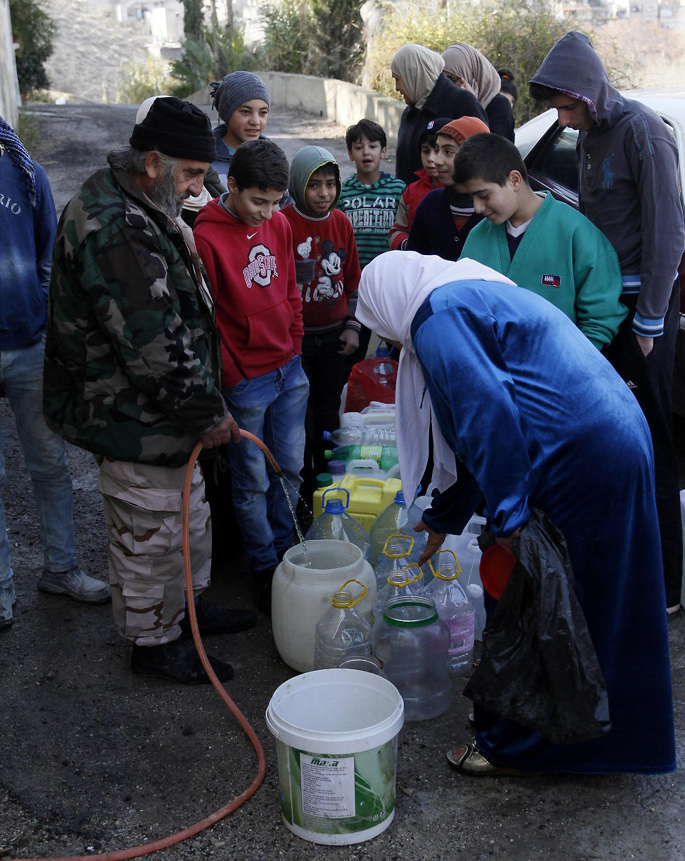 A Syrian soldier fills Jerrycans for Damascus residents (Photo: EPA)