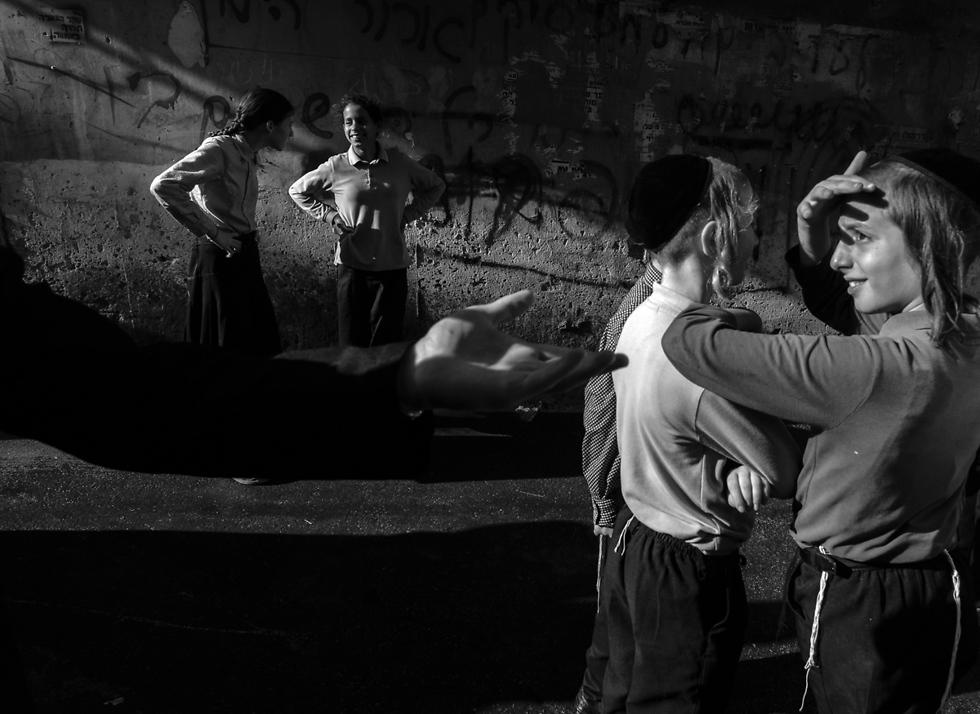 יד מסתורית, בנים ובנות על רקע קיר מתפורר עם גרפיטי (צילום: אילן בן יהודה) (צילום: אילן בן יהודה)