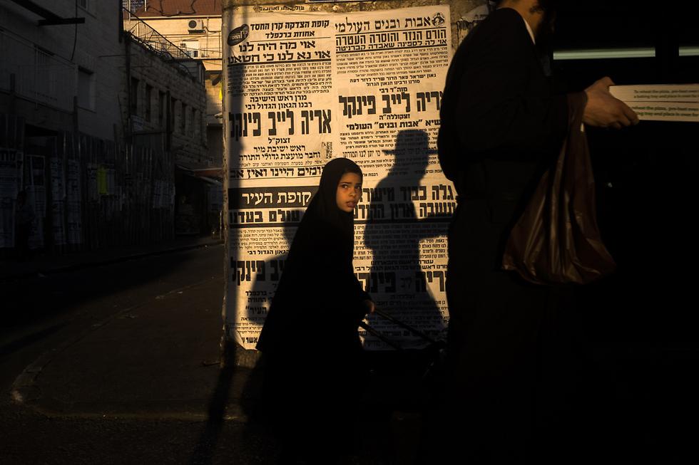 ילדה עטופה בשחור והצל של אבא שלה על רקע פשקווילים (צילום: אילן בן יהודה) (צילום: אילן בן יהודה)