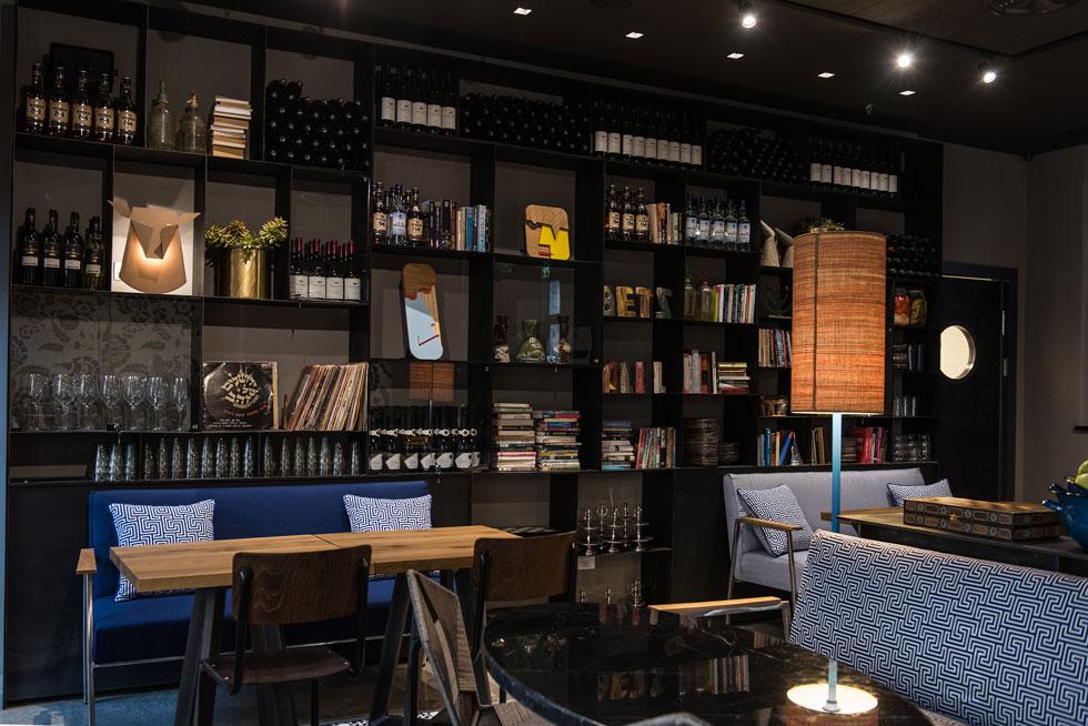 ספריית ברזל גדולה עם ספרות עברית, בקבוקי משקה וגם פריטי עיצוב ואמנות ישראליים, כמו המסיכות של צחי נבו ומנורת האייל של חן ביקובסקי (צילום: סיוון אסקיו)