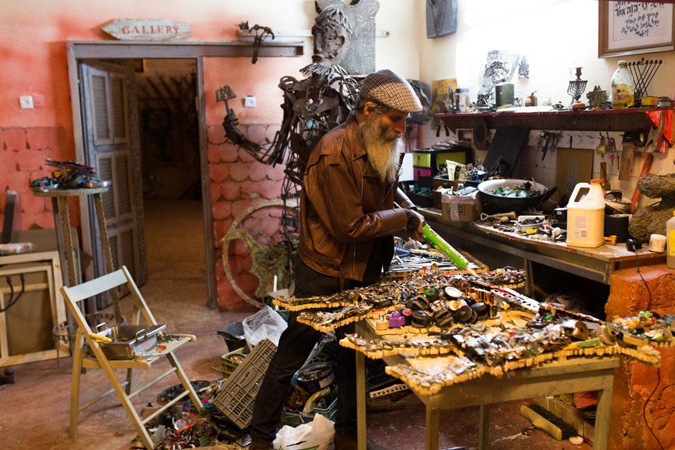 """אמיליו מוגילנר בסטודיו שלו ברחובות. """"הייתי מחביא חפצים ישנים, עד שהצטברה אצלי כמות גדולה, וכדי לצמצם אותה, התחלתי ליצור מהם"""" (צילום: אלון פרס)"""