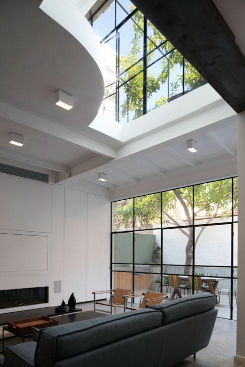 מעל הסלון תקרת זכוכית, ודרכה נראה קיר הזכוכית בשתי הקומות. מסך הטלוויזיה מוסתר בקיר, ותחתיו קמין (צילום: עדי גלעד)
