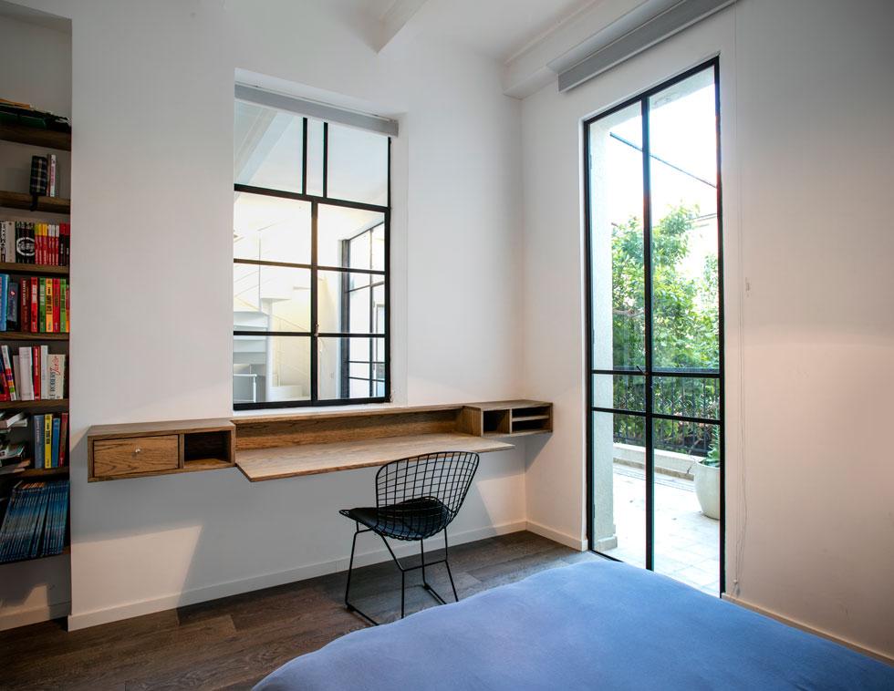 לאחד החדרים מרפסת צמודה, והוא משקיף אל פינת הטלוויזיה בקומה, עם גרם המדרגות הלולייני שעולה אל קומת ההורים (צילום: עדי גלעד)