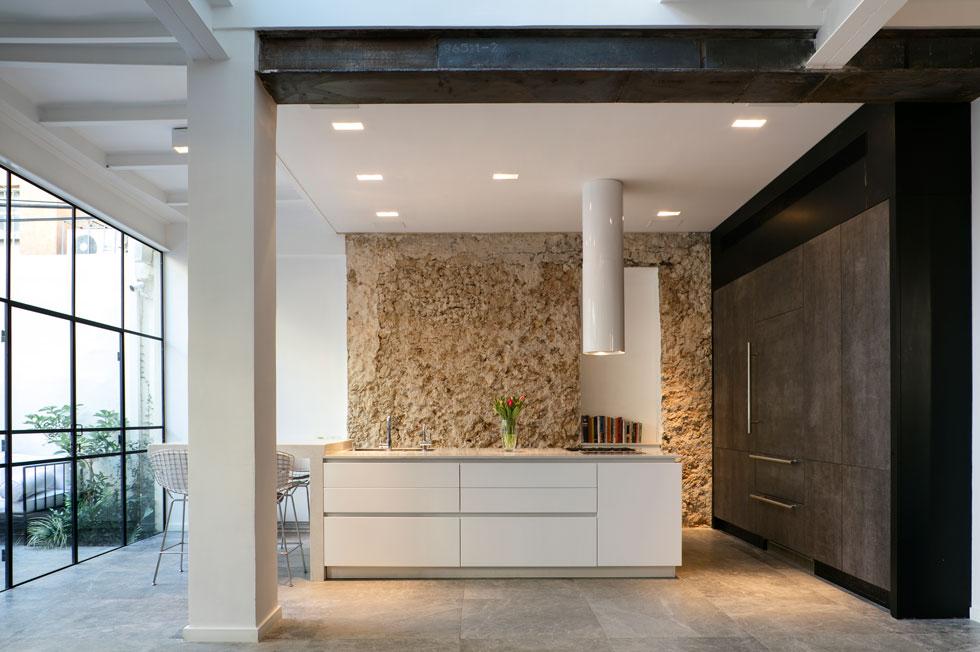 המטבח. קיר של ארונות שחורים ניצב לקיר מקורי, שנחשף בשיפוץ. הוא עשוי צדפים, חול ים ובטון, והוחלט להשאירו כרקע מחוספס ודומיננטי למטבח (צילום: עדי גלעד)