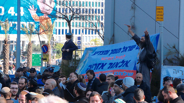Protesters with a sign that says 'The people of Israel support and salute to the hero soldier Elor Azaria' (Photo: Dana Kopel)