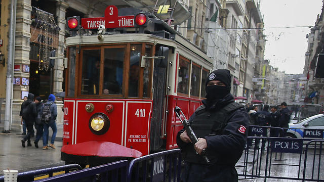 A tram is driven past as a Turkish police officer secures central Istanbul's Istiklal Avenue, the main shopping road of Istanbul.(Photo: AP)