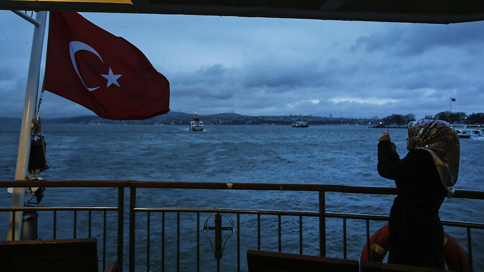 A woman takes pictures on a boat crossing the Bosporus in Istanbul. (Photo: AP)