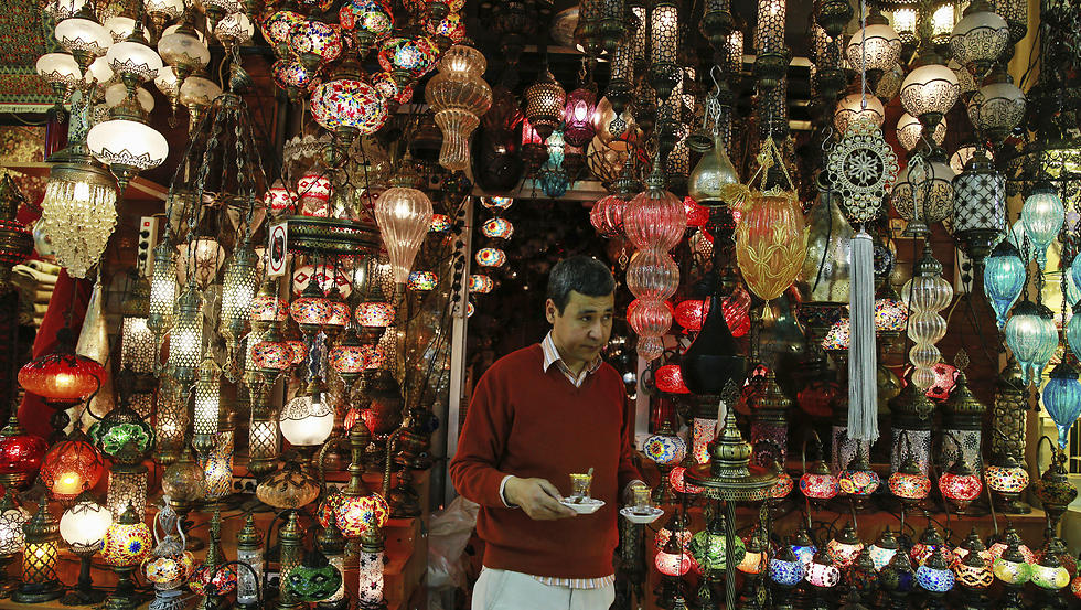 A shop owner holds cups of tea outside his shop in Istanbul's Grand Bazaar. (Photo: AP)