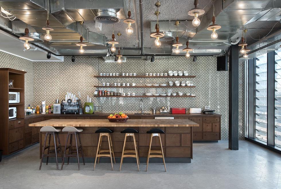 בקומה השביעית אין משרדים אלא מרחבים משותפים, כמו מטבח פתוח על רקע קיר של קרמיקה מאוירת. הרהיטים ביתיים בסגנונם, והמנורות קיבלו טוויסט אוריינטלי, עם צלחות בסיס מעץ סיסם הודי (צילום: עמית גושר)