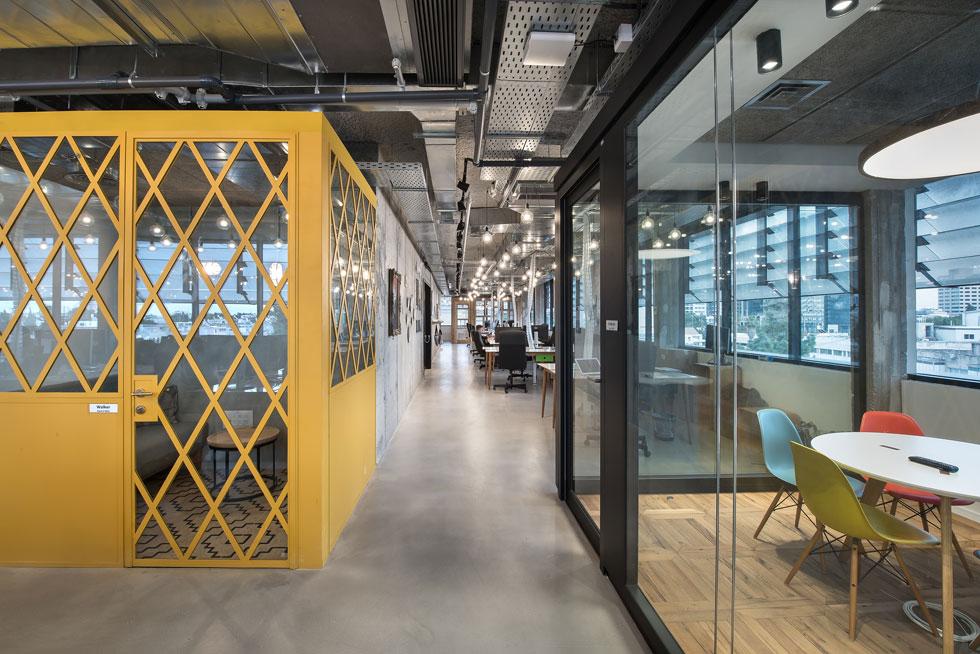 חדרים אחרים מוסגרו בפרופילים צהובים בדוגמת מעוינים גדולים, או בפלדה שחורה. גם הרצפה בהם שונה ומבדילה אותם מהסביבה (צילום: עמית גושר)